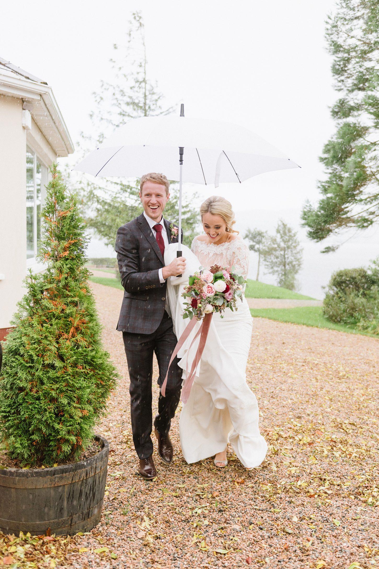 bride and groom with umbrellas on rainy wedding day